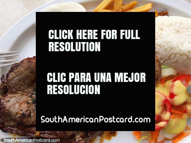 Carne, arroz, patatas, papas fritas, arepa y ensalada para almorzar en Girardot, una comida sencilla. (640x480px). Colombia, Sudamerica.