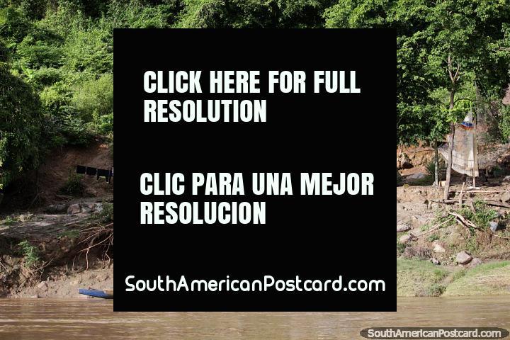 Casa junto al río y patio delantero con canoa de madera y secado de ropa, Río Magdalena, Girardot. (720x480px). Colombia, Sudamerica.