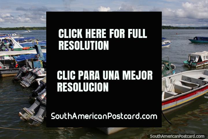 Grande barco de carga vermelho e barcos turïsticos em volta do porto e cais em Buenaventura. (720x480px). Colômbia, América do Sul.