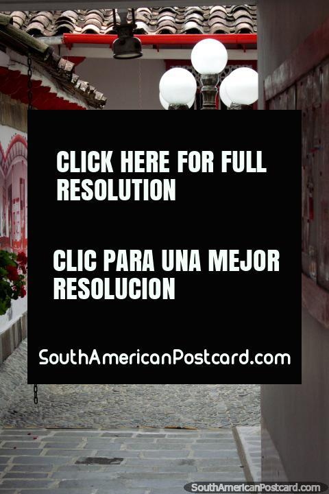 Entrada e pátio frontal do Hotel La Casona com paralelepípedos, luzes, pinturas e arte em Jardin. (480x720px). Colômbia, América do Sul.