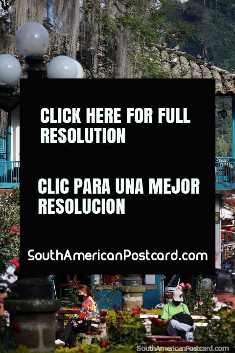 Edifício atraente com varanda e portas azuis brilhantes, localizado no parque no Jardin. (480x720px). Colômbia, América do Sul.