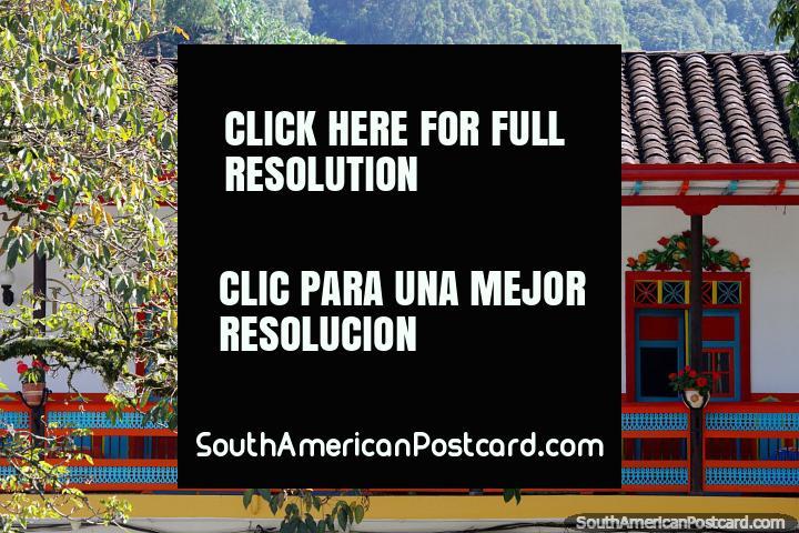 Balcón de madera colorido bajo un techo de tejas, una característica icónica de Jardin. (720x480px). Colombia, Sudamerica.