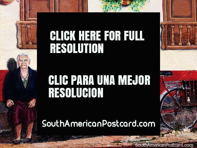 O homem e a mulher mais velhos estão sentados do lado de fora de uma casa, uma bicicleta ao lado, um mural na lateral de uma casa em Sogamoso. (640x480px). Colômbia, América do Sul.