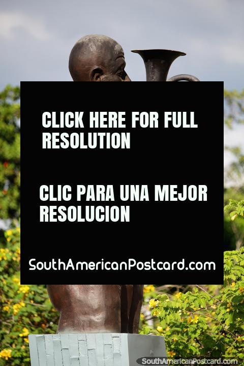 Homem sopra um instrumento de sopro, o monumento dos músicos em Monteria. (480x720px). Colômbia, América do Sul.