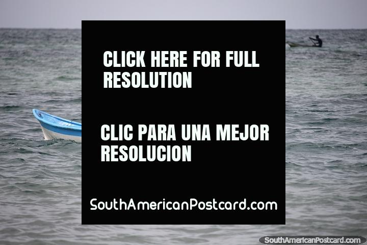 One man solo in a canoe at sea but he has a distant companion, locals of Tintipan Island. (720x480px). Colombia, South America.