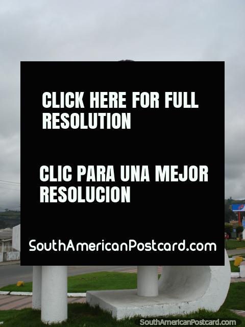 Homem com pá e monumento de cimento em Tulcan. (480x640px). Equador, América do Sul.