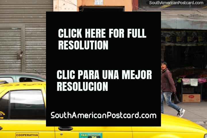 Fruit and vegetable shop, boy walks past, yellow taxi, Ambato. (720x480px). Ecuador, South America.