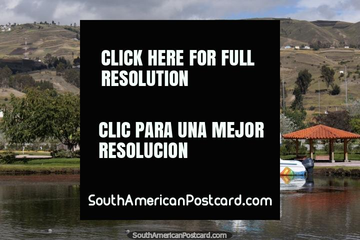 Um barco colorido senta-se na água na Lagoa Colta com colinas em fundo. (720x480px). Equador, América do Sul.