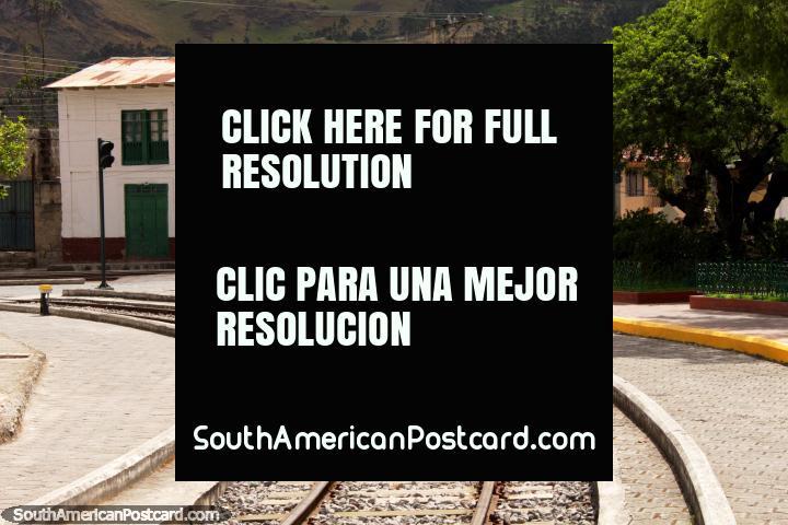 Um edifïcio histórico junto de um parque perto do trem segue a pista em Alausi. (720x480px). Equador, América do Sul.