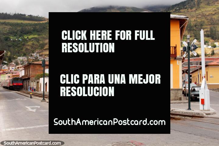 Pistas y edificios y un hombre en una bicicleta, frente a la estación de Alausí. (720x480px). Ecuador, Sudamerica.