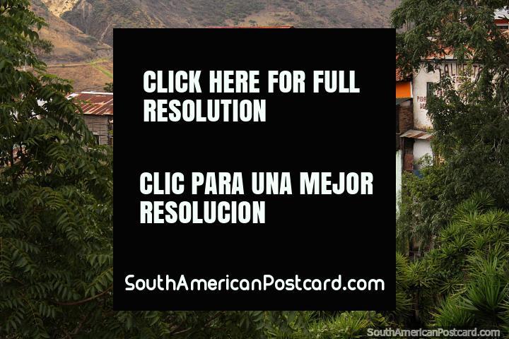 Uma pilha de casas de muitas cores entre a cidade e a ponte em Alausi. (720x480px). Equador, América do Sul.