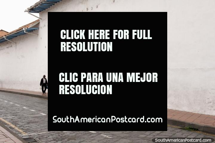 Man walks past a blue door along a long white wall in Cuenca. (720x480px). Ecuador, South America.