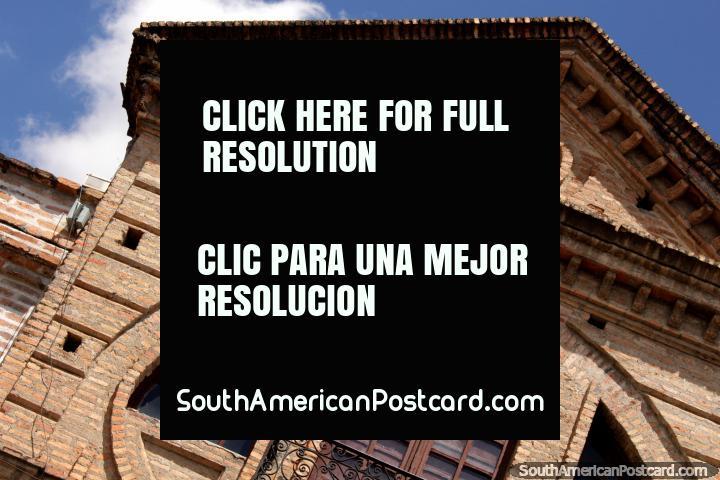 Fachada de ladrillos con un ojo de buey y ventanas redondeadas en Cuenca. (720x480px). Ecuador, Sudamerica.