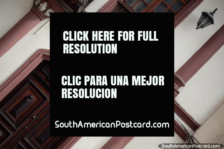 Dark wooden door and window, facade with columns and lamps in Cuenca, Gaban. (720x480px). Ecuador, South America.