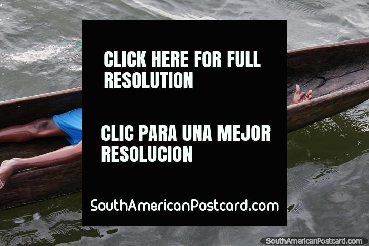 Young man laying back in a wooden canoe, having fun at the port in San Lorenzo. (720x480px). Ecuador, South America.
