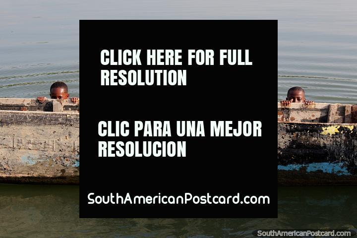 Os irmãos espreitam da sua canoa de madeira no Rio Esmeraldas. (720x480px). Equador, América do Sul.