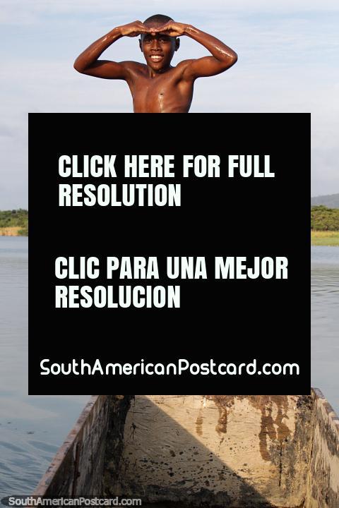 Gran pose aérea, niño saltando de una canoa al agua en el Río Esmeraldas. (480x720px). Ecuador, Sudamerica.