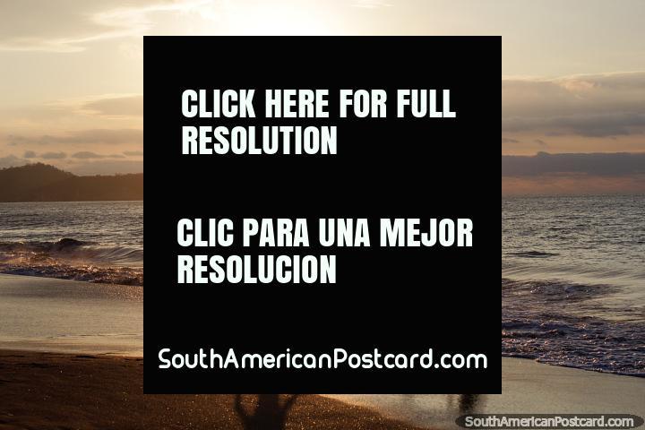 As crianças jogam no ocaso em praia de Atacames, Ilha de Pássaro na distância. (720x480px). Equador, América do Sul.