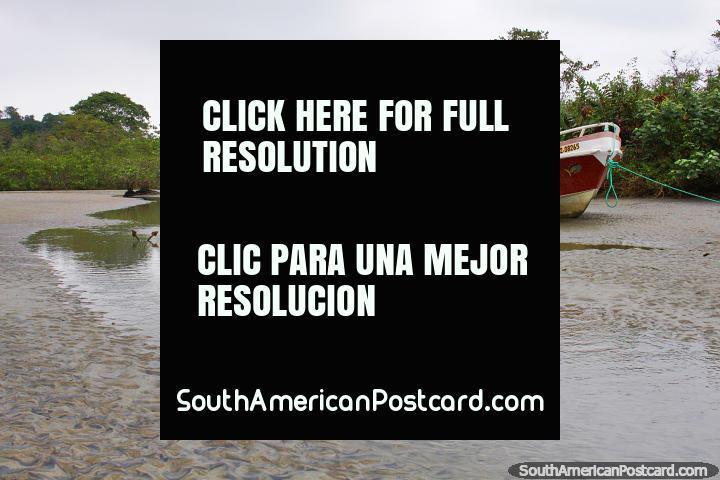 Uma entrada e um par de barcos em um dia cinza em Mompiche. (720x480px). Equador, América do Sul.