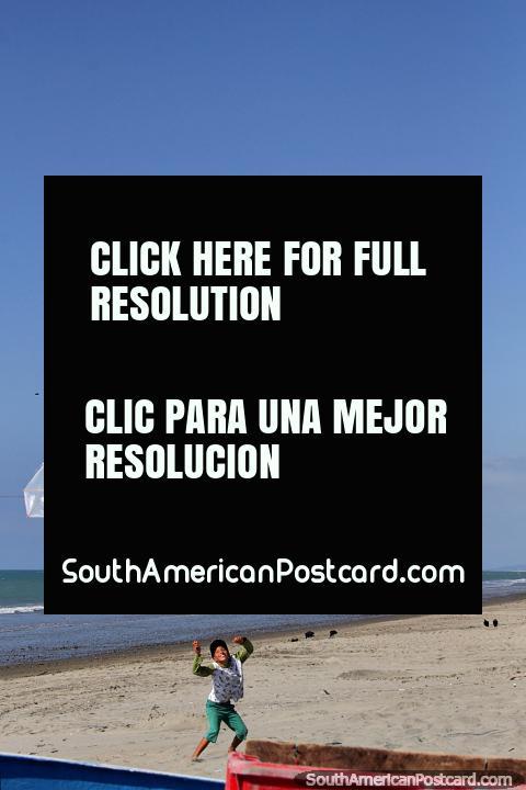 O rapaz voa um pequeno papagaio de papel em um grande céu na praia em El Matal. (480x720px). Equador, América do Sul.