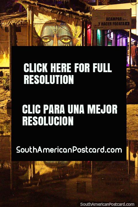 Cara grande, arte callejero con reflejo junto a un bar y la playa en Montañita. (480x720px). Ecuador, Sudamerica.