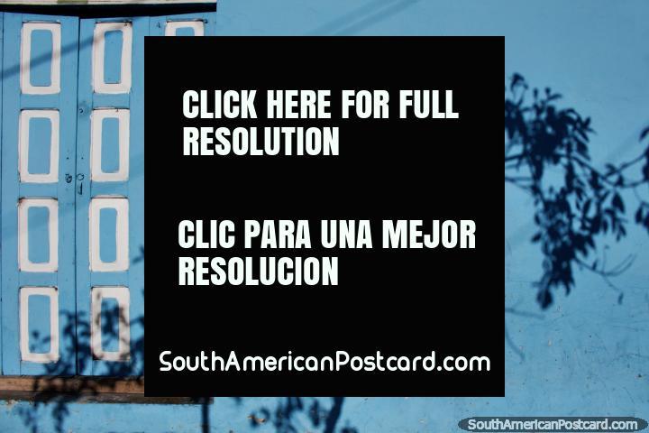 Light blue facade, checkered wooden door and fantastic shadow of a tree in Banos. (720x480px). Ecuador, South America.