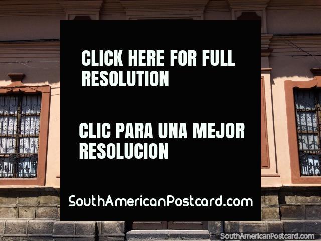 Edifïcio histórico com pano para saia de pedra e de madeira e porta de ferro em Latacunga. (640x480px). Equador, América do Sul.