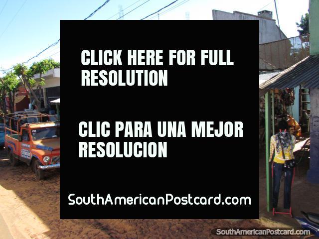 Tiendas y pequeño camión rojo en el adoquín avenida central a través de Santa Rosa. (640x480px). Paraguay, Sudamerica.