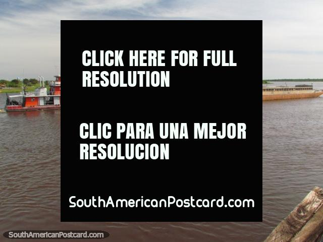 Orange tugboat 'Don Manuel' pushes barge 'Leticia' on the Paraguay River in Concepcion. (640x480px). Paraguay, South America.