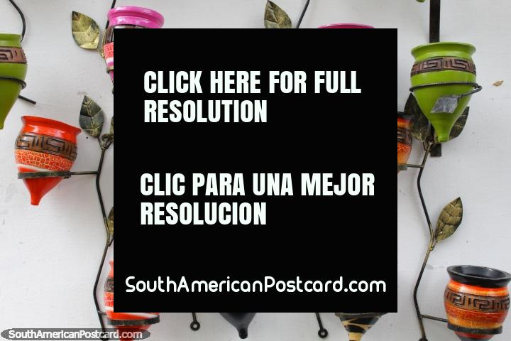 Colorful ceramic plant holders shaped like spinning tops, wall display in Aregua. (720x480px). Paraguay, South America.