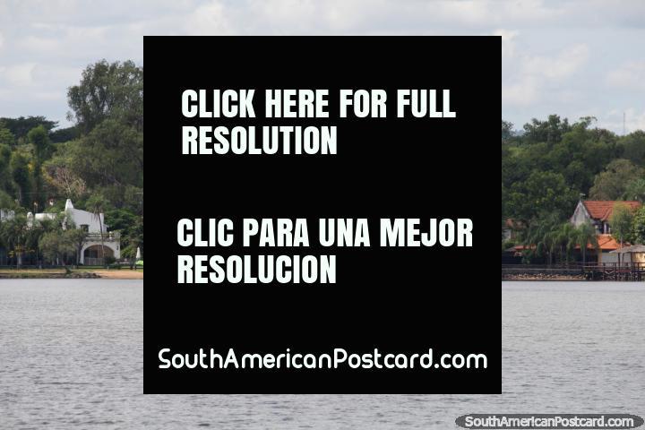 Casas e terra do arbusto na borda do lago em San Bernardino, fuga de férias. (720x480px). Paraguai, América do Sul.