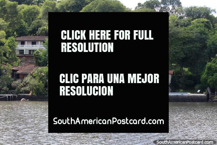 Casas con clase rodeados por arbustos al lado del lago en San Bernardino. (720x480px). Paraguay, Sudamerica.