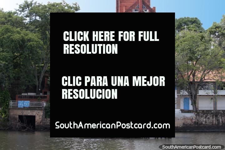 Hotel do Sol atrás de casas de margem de lago em San Bernardino. (720x480px). Paraguai, América do Sul.