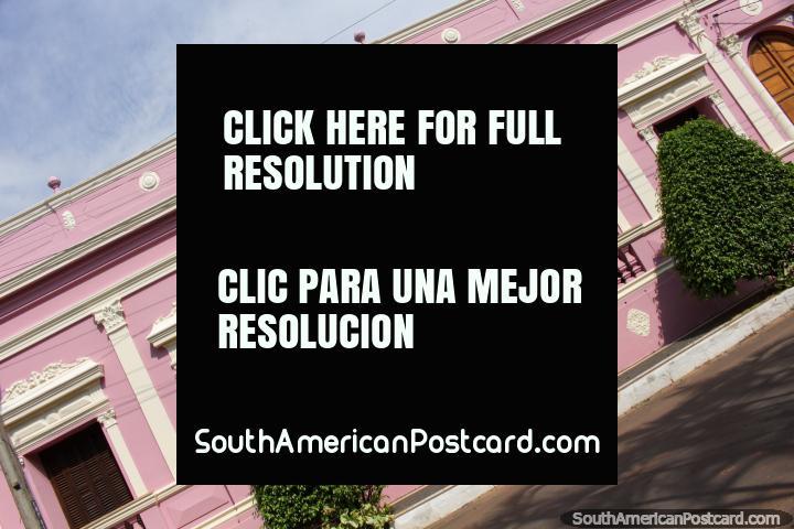 Arboles de cobertura verde delante de la sede del club de color rosa en Villarrica. (720x480px). Paraguay, Sudamerica.