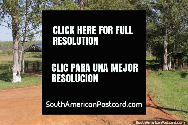 Una mujer comienza su pie por un largo camino de tierra en el campo, al norte de Villarrica. (720x480px). Paraguay, Sudamerica.