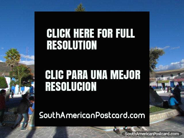 Locals of Celendin enjoy the park, beside fountain, clock tower behind. (640x480px). Peru, South America.