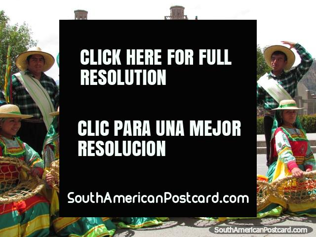 Women in traditional dress and baskets, men in green with hats, Huaraz. (640x480px). Peru, South America.