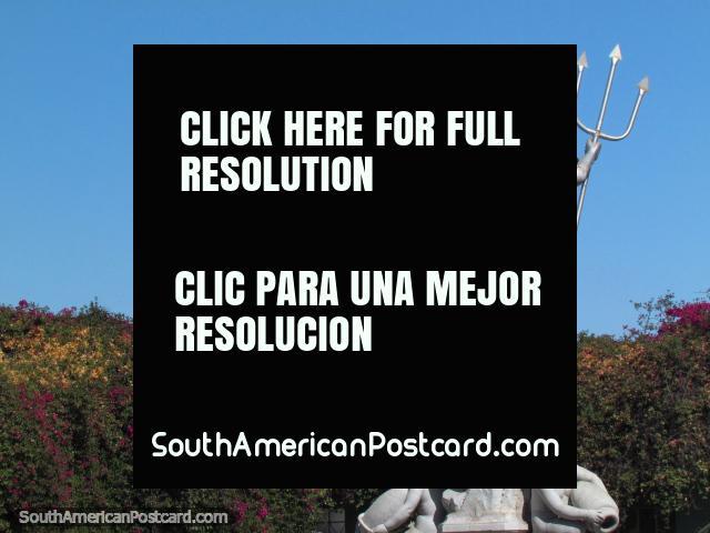 Uma sebe com flores purpúreas e amarelas e uma estátua de um homem com um forcado, Arequipa. (640x480px). Peru, América do Sul.