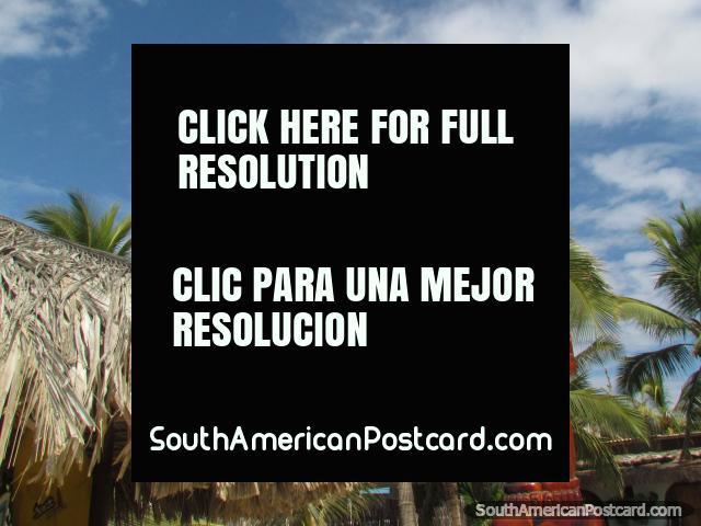 Figura de madeira esculpido em frente de palmeiras e uma cabana em Mancora. (640x480px). Peru, América do Sul.
