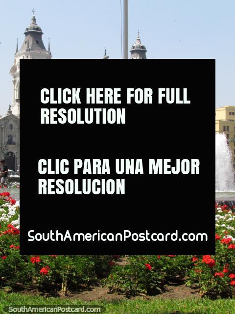 A catedral de Lima atrás de um canteiro de flores vermelhas e brancas e uma fonte. (480x640px). Peru, América do Sul.