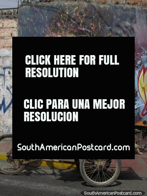 Um velho homem com várias cães anda passado alguma arte de grafite em Tacna. (480x640px). Peru, América do Sul.