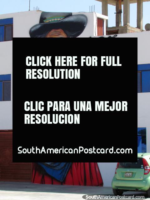 Pintura mural fantástica y enorme de una mujer indígena con telas tradicionales y sombrero en Tacna. (480x640px). Perú, Sudamerica.