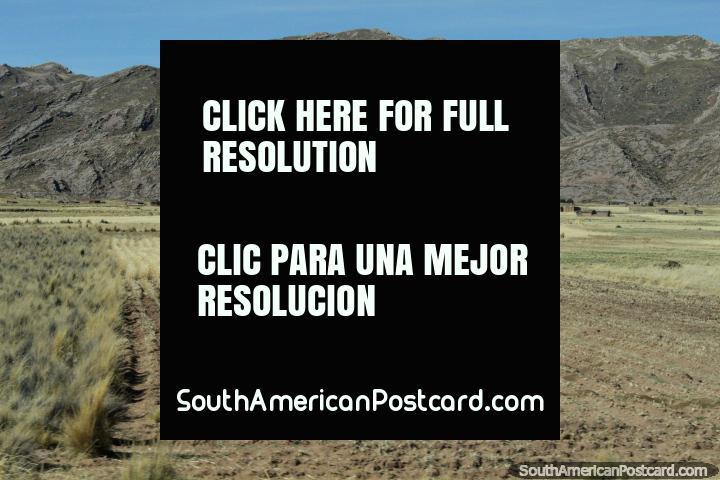 Pastagens e casas na distância em baixo de colinas rochosas, ao oeste de Desaguadero. (720x480px). Peru, América do Sul.