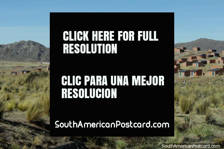 Casas de ladrillo pequeñas y montañas nevadas en la distancia alrededor de Desaguadero, la ciudad fronteriza de Perú y Bolivia. (720x480px). Perú, Sudamerica.
