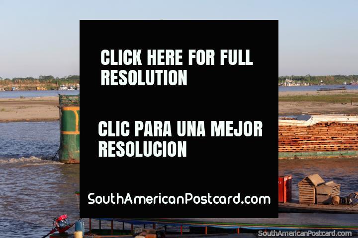 Barco lleva grandes pizarras de madera abajo el rio en Pucallpa. (720x480px). Perú, Sudamerica.