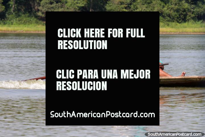 A mulher nativa dirige a sua canoa ao longo do lago em Lago Yarinacocha em Pucallpa. (720x480px). Peru, América do Sul.