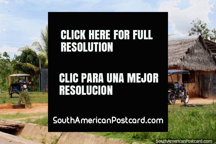 Thatched roof houses, palm trees and mototaxis, Amazon living, south of Yurimaguas. (720x480px). Peru, South America.