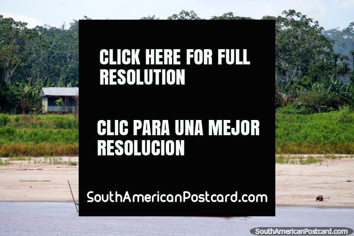 Canoa fluvial motorizada y casas Amazónicas distantes, al sur de Lagunas. (720x480px). Perú, Sudamerica.