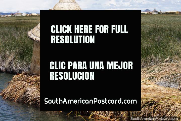 Ao redor de cabana coberta com palha que se senta em canas flutuam junto das águas em Lago Titicaca em Puno. (720x480px). Peru, América do Sul.