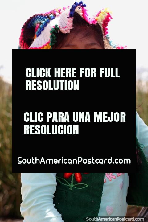 Young Uros girl with traditional head wear and a big smile at Suma Kurmi Island in Puno. (480x720px). Peru, South America.